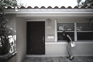 A woman shopping for a new home looks at a foreclosed property.