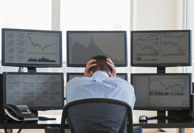 New day trader contemplating stocks in front of computer monitors.