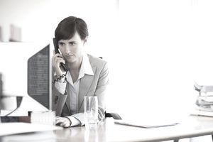 Businesswoman working at computer and talking on phone