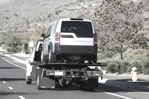 A repossessed car on the flat bed of a tow truck driving down a street.