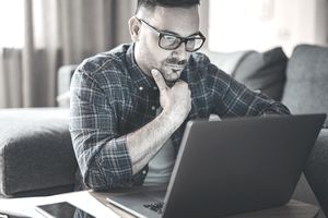 Man wearing spectacles working on a laptopn