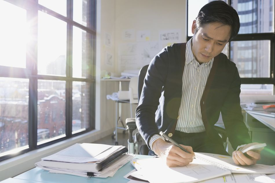 Man making calculations in high rise office