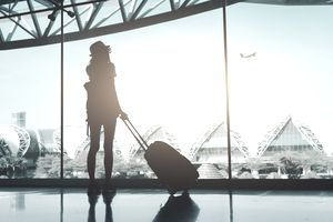 Silhouette of Woman With Luggage Standing In Airport