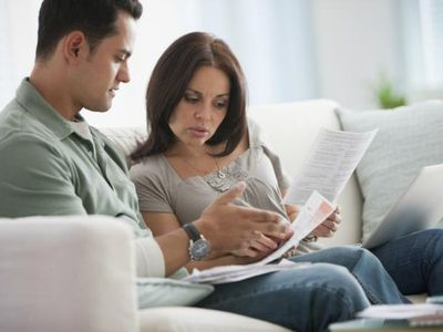 Young couple going over their financial budget to determine if they can live off of one income while sitting on their couch
