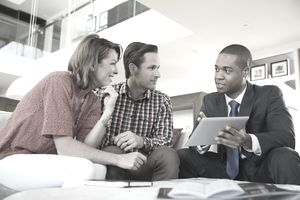 Couple talking to financial advisor at a coffee table