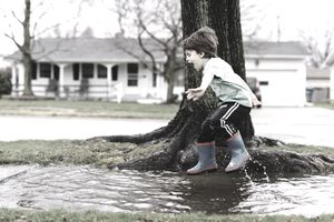 Boy jumping in water conceptual taking control of flood insurance