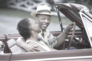 A man in a straw fedora looks adoringly at his wife as they drive a convertible
