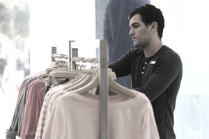 Retail worker stocking a store full of clothing products