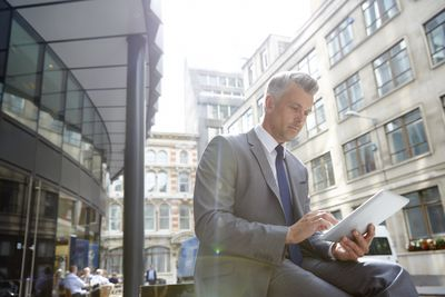 Man in suit looking at tablet