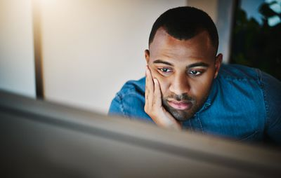 Shot of a young businessman looking bored while working during a late night in a modern office