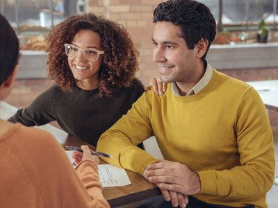 A young couple gets advice about refinancing their mortgage.