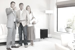 male real estate agent talking to couple showing them a house