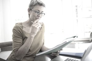 A woman reviews financial plans in folders.