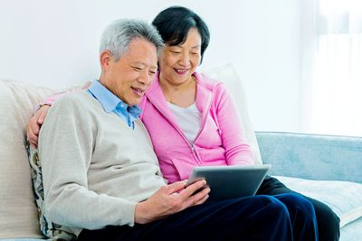 Smiling retired couple seated together on sofa looking at a tablet