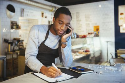 Deli owner using smartphone while writing on clipboard