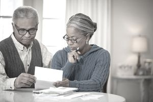 Two older people looking at a paper statement