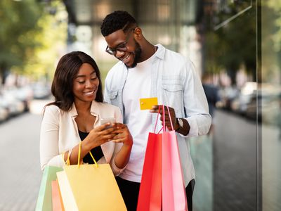 Young couple holding shopping bags, smartphone, and credit cards