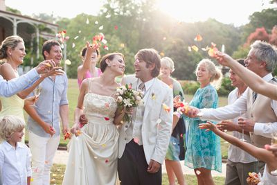 Newlyweds surrounded by people throwing confetti