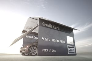 Car driving out of garage made of credit cards