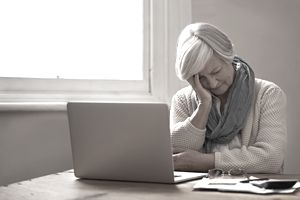 Elderly woman looking frustrated while reviewing financial documents with a laptop