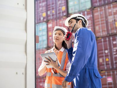 two pPeople with helmets discussing products in front of a shipping container dock
