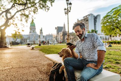 Mature man with beard and stylish casual clothing in springtime day in Buenos Aires, Argentina walking his dog
