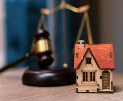 Small-scale home in front to a judge's gavel, depicting how a judgment can seize property