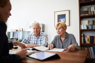 An older couple meets with a credit counselor to review their debt relief options.