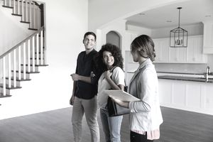 First time homebuyers with a realtor check out an empty, open floorplan home