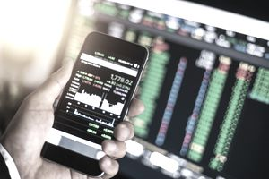 person looking at phone and computer screen with stock market graphs displayed