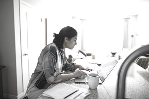Woman in Brown Plaid Shirt Working on Laptop at Kitchen Counter