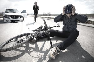 A bicyclist holds his helmeted head while sitting in the street after being hit by a car. The driver of the car runs toward him.