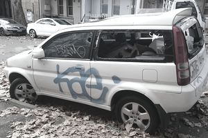 Vandalized car with broken window parked next to the sidewalk