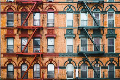 Brick apartment building featuring three storeys and fire escapes