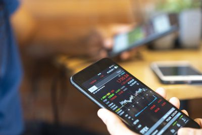 Day Trader looking at stock data on a smartphone