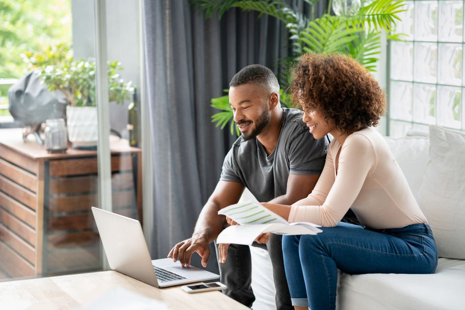 Loving African American couple paying bills online at home