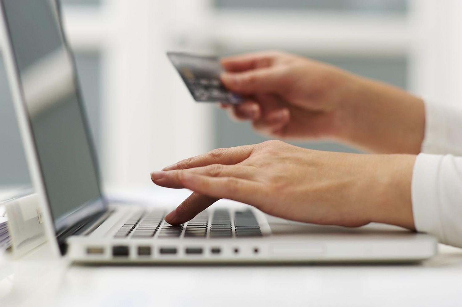 Close-up of woman's hands holding a credit card and entering info on a laptop
