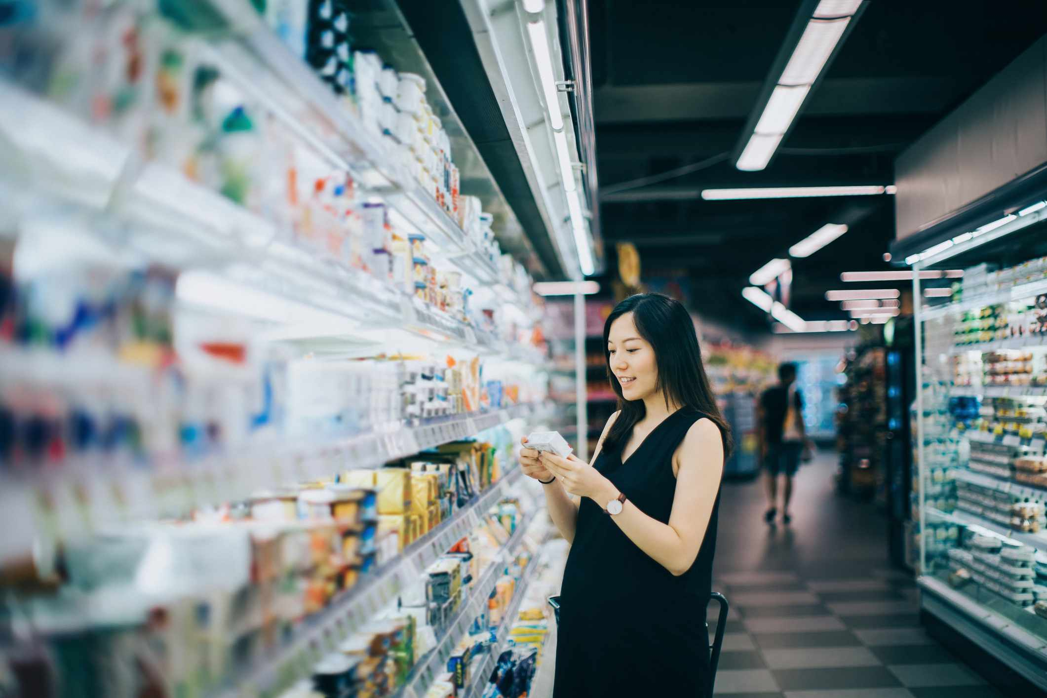 Pregnant woman shopping in supermarket and reading nutrition label
