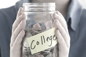 Young man holding jar of money labeled college