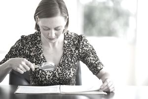 Woman looking at documents through a magnifying glass