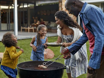 A family enjoys a barbecue in their yard.