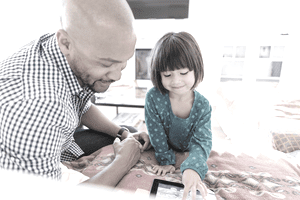 parent and child working together on a tablet