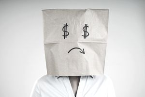 Woman wearing a paper bag with a sad face on it and dollar signs for eyes