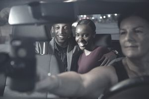 A couple smiles in the backseat as their rideshare driver adds their destination to her phone