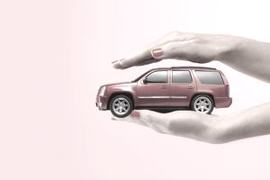 Woman holding a model of a car in one hand and covering it with the other to represent car insurance from The General.