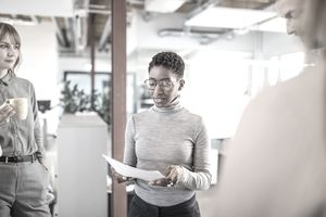 A woman looks at paperwork in her workplace.