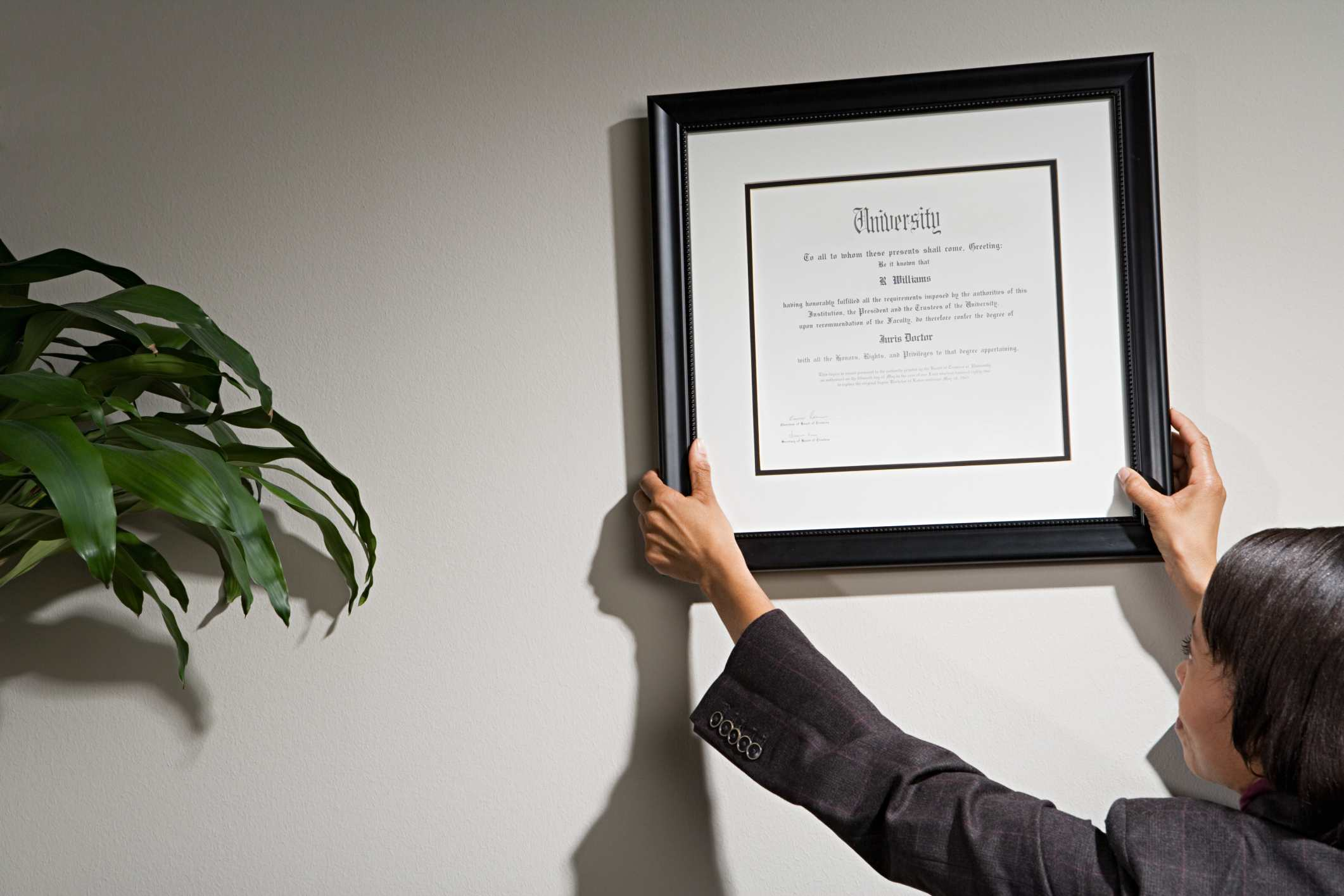 Financial advisor hanging credentials on the wall.