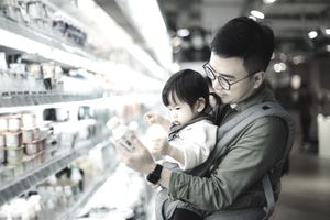 Father with little daughter grocery shopping for dairy products in supermarket