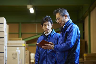 Japanese male workers in a warehouse.