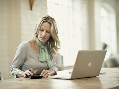 Woman using calculator and laptop